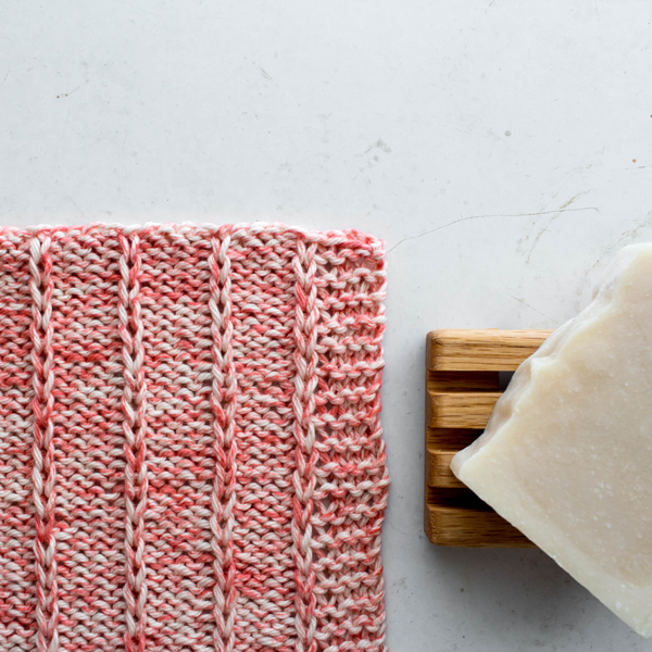 knitted dishcloth with soap bar laying on white table