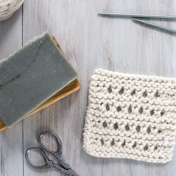 small knitted dishcloth with soap, scissors and knitting needles