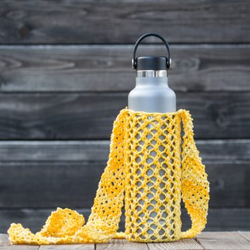 Knitted yellow water bottle sling in a hydro flask.